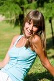 De gelukkige vrouw geniet van zon in park stock afbeeldingen