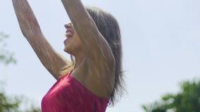 De gelukkige vrouw geniet de zomer van regen in langzaam motie koud water door zonneschijnschreeuw stock videobeelden