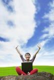 De gelukkige vrouw heft handzitting met openlucht laptop op Stock Afbeelding