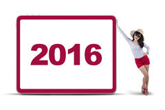 De gelukkige vrouw leunt aan boord met nummer 2016 Stock Foto
