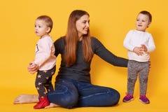 De gelukkige vrouw, liitle tweelingmeisjes, moeder en haar peuters, probeert om foto, zuigelingenspel met brij te maken, stelt in royalty-vrije stock foto
