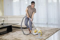 De gelukkige vrouw maakt tapijt met een stofzuiger schoon royalty-vrije stock foto's