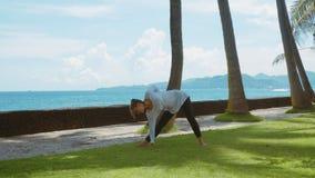 De gelukkige vrouw maakt yogapraktijk via saldooefening, stelt de strijder, meditatie, ontspanning op het overzeese strand met aa stock footage