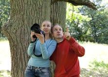 De gelukkige vrouw met de camera en de man toont omhoog Stock Afbeeldingen