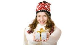 De gelukkige vrouw met de winter GLB houdt gift in handen Stock Afbeelding