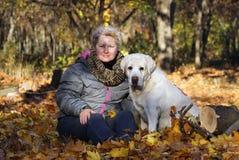 de Gelukkige Vrouw met Geel Labrador in Autumn Park In de zonnige dag stock foto's