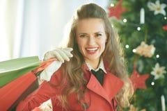 De gelukkige in vrouw met het winkelen doet dichtbij Kerstboom in zakken royalty-vrije stock foto