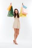 De gelukkige Vrouw met het Winkelen doet in zakken Op wit stock afbeeldingen