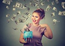 De gelukkige vrouw met spaarvarken viert succes onder geldregen die onderaan dollarrekeningen vallen Stock Afbeeldingen