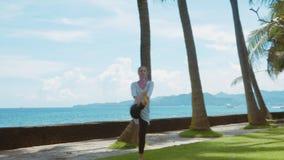 De gelukkige vrouw oefent yoga, saldooefening, het uitrekken zich been uit, stelt de strijder, op het strand, mooie achtergrond,  stock footage