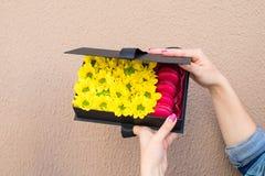 De gelukkige vrouw ontving een zwarte giftdoos met zonnebloemen en helder Royalty-vrije Stock Foto's