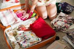 De gelukkige vrouw pakt zorgvuldig kleren in koffer in stock afbeeldingen