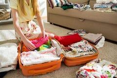 De gelukkige vrouw pakt zorgvuldig kleren in koffer in stock foto's
