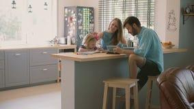 De gelukkige vrouw spreekt aan haar echtgenoot en bevestigt haar dochtershaar bij de keukenlijst Langzame Motie stock videobeelden