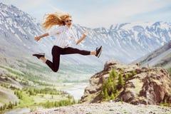 De gelukkige vrouw springt bergenreis Stock Afbeelding