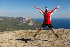 De gelukkige vrouw springt op een piek van een berg in de zomertijd in bergen genietend van de klim met mooie rotsachtig en overz Royalty-vrije Stock Foto's