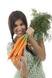 De gelukkige vrouw toont op een bos van wortelen Royalty-vrije Stock Afbeeldingen