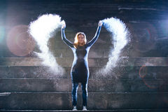 De gelukkige vrouw werpt wit poeder in vorm van engelenvleugels Royalty-vrije Stock Foto