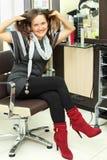 De gelukkige vrouw zit in leunstoel en raakt haar haar Royalty-vrije Stock Foto