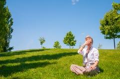 De gelukkige vrouw zit op grasgazon De mooie vrouw van de bohostijl met toebehoren geniet de zomer van zonnige dag in park royalty-vrije stock foto's