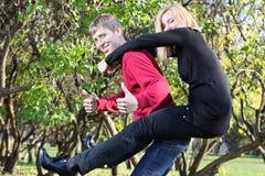 De gelukkige vrouw zit op rug van de mens en man duimen omhoog in park Stock Afbeeldingen