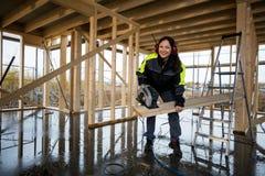 De gelukkige Vrouwelijke Elektrische Zaag van Timmermanscutting wood with bij Plaats stock foto
