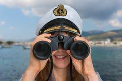 De gelukkige vrouwelijke kapitein kijkt door verrekijkers Royalty-vrije Stock Foto's