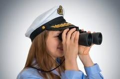 De gelukkige vrouwelijke kapitein kijkt door verrekijkers Stock Fotografie