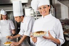 De gelukkige Vrouwelijke Keuken van Chef-kokpresenting pasta in Stock Foto's