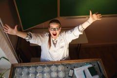 De gelukkige vrouwelijke wetenschapper die haar opheffen dient haar laboratorium in stock afbeeldingen