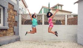 De gelukkige vrouwen die voor tuin springen schermen stock fotografie