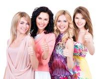 De gelukkige vrouwen met duimen ondertekenen omhoog stock afbeelding