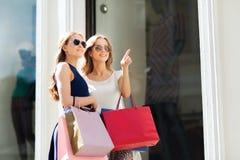 De gelukkige vrouwen met het winkelen doet in openlucht in zakken Royalty-vrije Stock Afbeeldingen