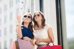 De gelukkige vrouwen met het winkelen doet in openlucht in zakken Royalty-vrije Stock Foto