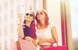 De gelukkige vrouwen met het winkelen doet in openlucht in zakken Stock Afbeelding