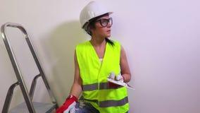 De gelukkige vrouwenbouwvakker dichtbij muur toont duim stock videobeelden