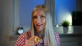 De gelukkige vrouwenholding die bitcoin beduimelt omhoog tonen Vrolijke jonge blonde vrouw die in vrijetijdskleding bij donker ve stock videobeelden