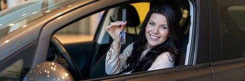 De gelukkige vrouwenkoper onderzoekt haar nieuw voertuig in het autohandel drijven royalty-vrije stock afbeelding