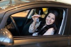 De gelukkige vrouwenkoper onderzoekt haar nieuw voertuig in het autohandel drijven stock afbeelding