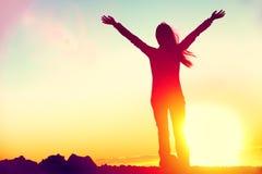 De gelukkige wapens van de succes winnende vrouw omhoog bij zonsondergang royalty-vrije stock foto's