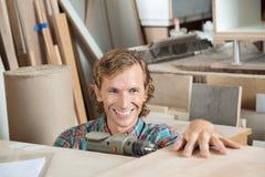 De gelukkige Workshop van Timmermansdrilling wood in royalty-vrije stock foto's