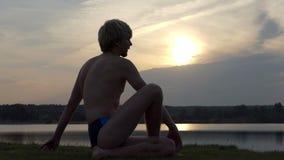 De gelukkige yogi zit in een adelaarspositie inzake een meerbank in slo-mo stock videobeelden