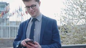 De gelukkige zakenman verzendt een bericht gebruikend een smartphone stock videobeelden