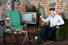 De gelukkige zingende mens in grote witte hoofdtelefoons luistert oude radio Royalty-vrije Stock Foto