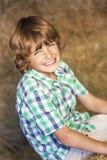 De gelukkige Zitting die van het Jongenskind op Hay Bales glimlachen stock afbeeldingen