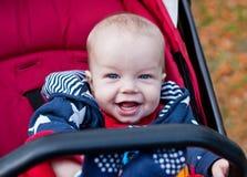 De gelukkige zitting van de babyjongen in een wandelwagen Stock Afbeeldingen