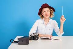 De gelukkige zitting van de meisjesfotograaf bij de lijst Het jonge mooie meisje in de witte camera van de kledingsholding en de  Stock Afbeeldingen