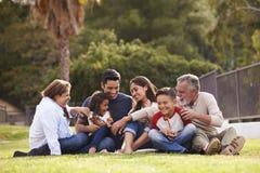 De gelukkige zitting van de drie generatie Spaanse familie op het gras samen in het park, selectieve nadruk royalty-vrije stock afbeeldingen