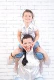 De zitting van het meisje op de hals van zijn moeder royalty-vrije stock foto's