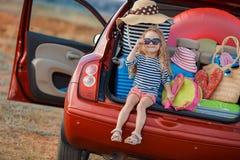 De gelukkige zitting van het babymeisje in de autoboomstam Stock Fotografie